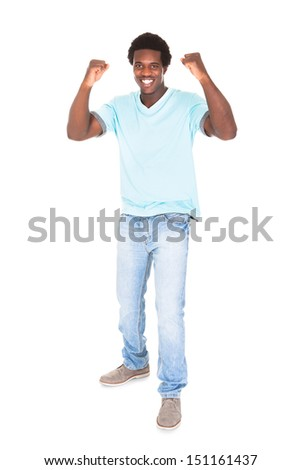 Excited Casual Young African Man Clenching His Fist Isolated Over White Background - stock photo