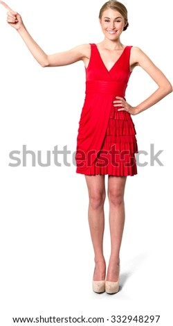 Excited Caucasian young woman with medium blond hair in evening outfit pointing using finger - Isolated - stock photo