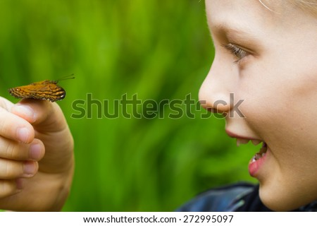 Excited child holding a butterfly on his hand with copy-space - stock photo