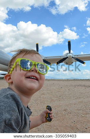 Excited child wearing sunglasses at an airport with a large jet or airplane in the background - stock photo