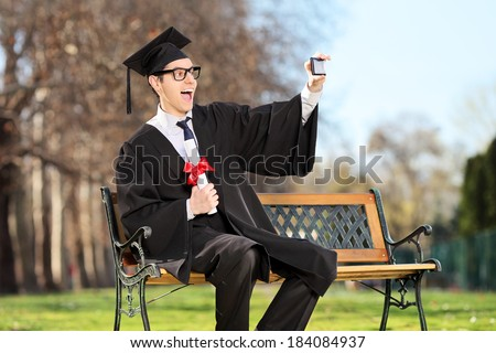 Excited college student taking a selfie in park  - stock photo