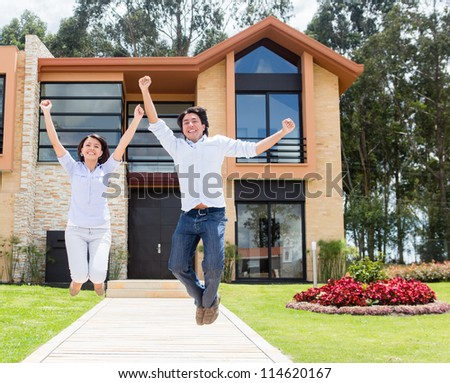 Excited couple jumping after buying a house - stock photo