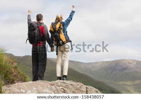 Excited couple reaching the top of their hike and cheering in majestic mountain scenery - stock photo