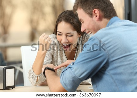 Excited couple reading e-mail with good news in a smartwatch in a coffee shop with a window in the background with a sunset light outdoors - stock photo