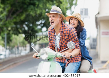 Excited couple riding moped in city - stock photo
