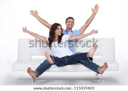 Excited couple sat on sofa with arms in the air - stock photo