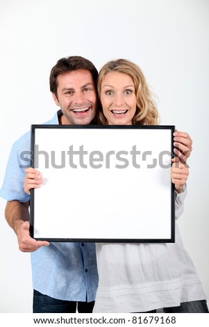 Excited couple with blank picture frame - stock photo
