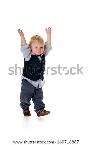 Excited cute blond toddler holds up arms, isolated on white - stock photo
