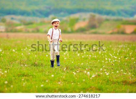 excited cute boy running blooming field, spring countryside - stock photo