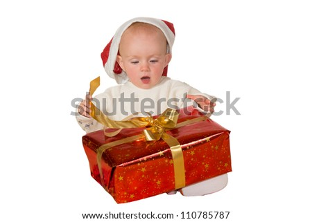 Excited cute little baby in a Santa hat untying a gold bow on a large red Christmas gift isolated on white - stock photo