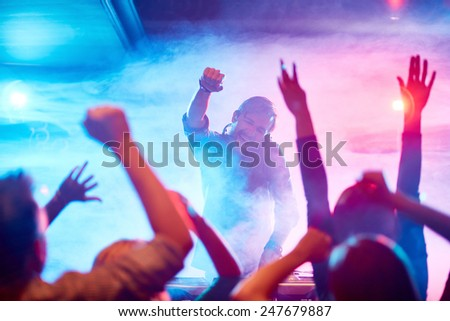 Excited deejay encouraging dancing crowd in nightclub - stock photo