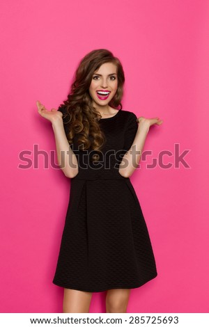 Excited elegance woman in black mini dress standing with arms outstretched. Three quarter length studio shot on pink background. - stock photo