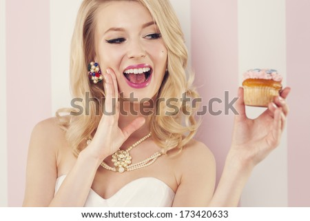Excited elegant woman with muffin  - stock photo
