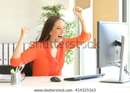 Excited entrepreneur wearing an orange blouse reading good news on line in a desktop computer monitor in the office - stock photo