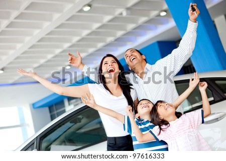 Excited family at the dealer buying a car and celebrating - stock photo