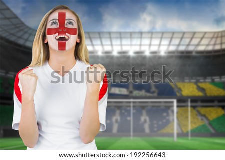 Excited fan england in face paint cheering against football pitch in large stadium - stock photo