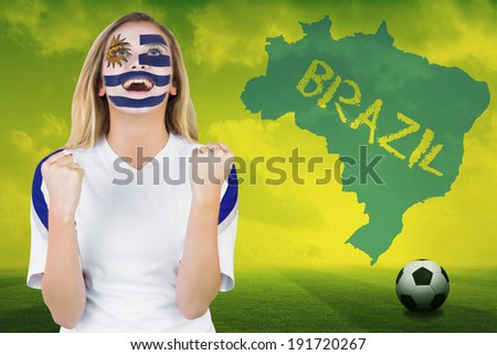 Excited fan in uruguay face paint cheering against football pitch with brazil outline and text - stock photo