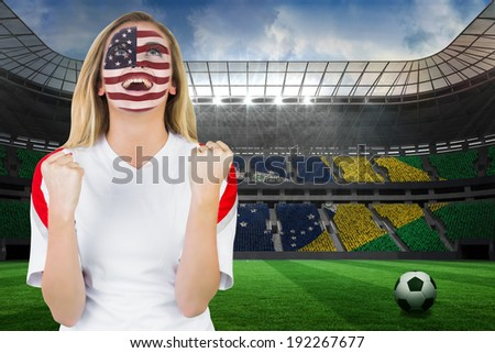 Excited fan in usa face paint cheering against large football stadium with brasilian fans - stock photo