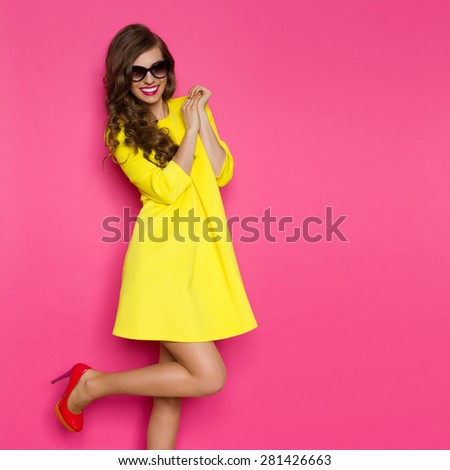Excited Fashion Girl. Smiling beautiful woman in yellow mini dress posing on one leg against pink background. Three quarter length studio shot. - stock photo