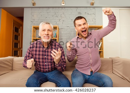 Excited father and son sitting on the sofa and watching football - stock photo