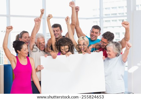 Excited fit people holding blank billboard against window at gym - stock photo