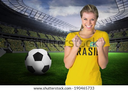 Excited football fan in brasil tshirt against large football stadium with fans in yellow - stock photo