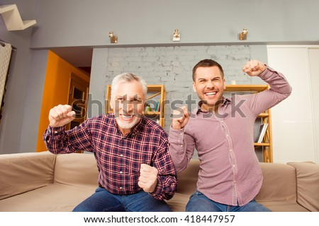 Excited football fans watching play with raised fists - stock photo