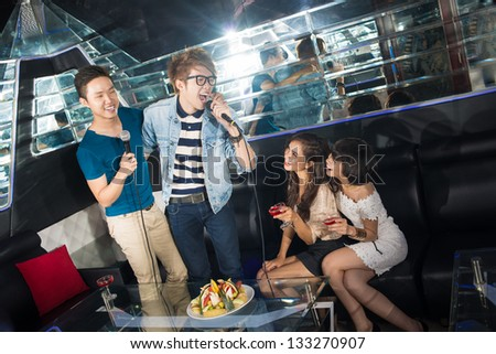 Excited friends having a karaoke party knocking themselves out - stock photo