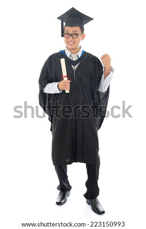 Excited full length Southeast Asian university student in graduation gown, standing isolated on white background. - stock photo