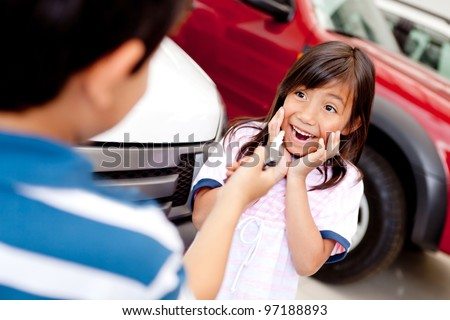 Excited girl buying a car at the dealer and looking at keys - stock photo
