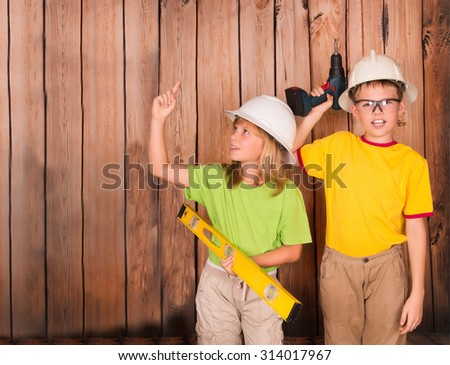 Excited girl pointing a great idea. Construction and renovation concept. Happy children in hardhats with tools on wooden background with copyspace.  - stock photo