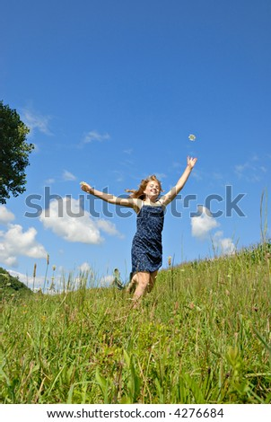Excited girl, running in a green field, tossing flower in air - stock photo