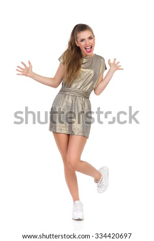 Excited Girl Standing On One Leg. Shouting young woman in gold mini dress and white sneakers standing on one leg with arms outstretched. Full length studio shot isolated on white. - stock photo