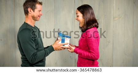 Excited girlfriend taking gift from boyfriend against wooden planks - stock photo