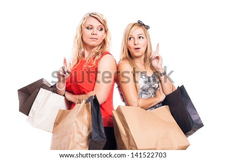 Excited girls holding shopping bags and pointing up, isolated on white background - stock photo
