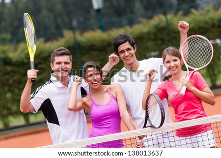 Excited group of tennis players with arms up - stock photo