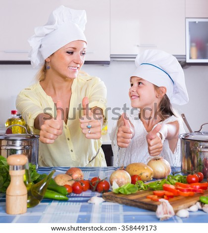 Excited happy adult american mom and daughter cooking vegeterian dish indoors - stock photo
