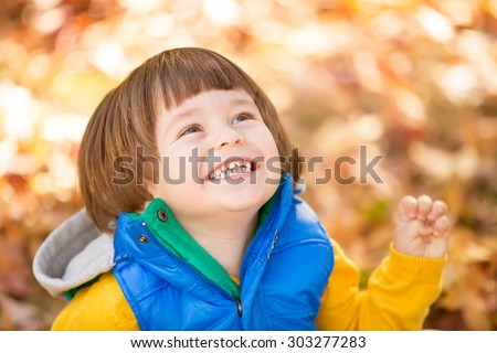 Excited happy baby enjoying autumn fall in the park - stock photo