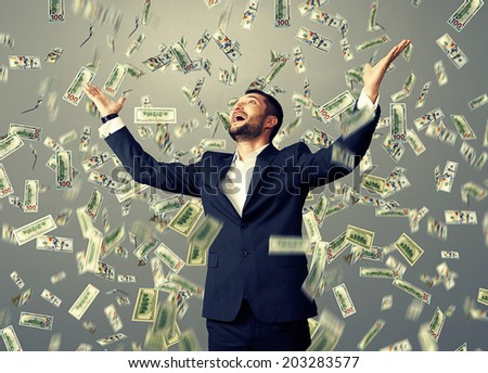 excited happy businessman standing under dollar's rain and looking up - stock photo
