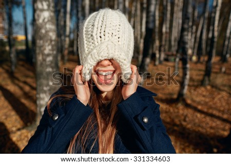 Excited happy fall woman smiling joyful and blissful pull knitted hat outside in colorful fall forest. Beautiful energetic caucasian young woman - stock photo
