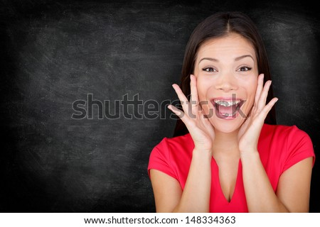 Excited happy woman by blackboard / chalkboard screaming with joy your message with copy space for text. Beautiful young asian multiracial causal female in red on black background. - stock photo