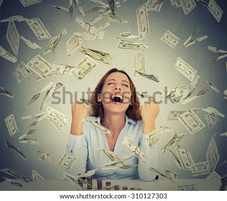 Excited happy young woman sitting at table with growing stack of coins under a money rain isolated on gray wall background. Positive emotions financial success luck good economy concept - stock photo
