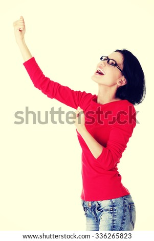 Excited happy young woman with fists up - stock photo