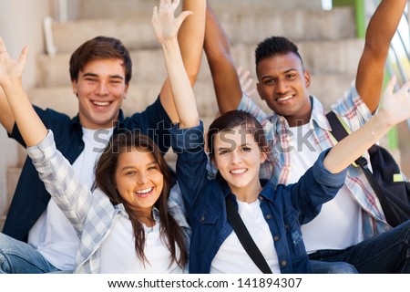 excited high school students with arms outstretched outdoors - stock photo