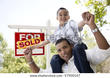 Excited Hispanic Father and Son in Front of Sold For Sale Real Estate Sign. - stock photo
