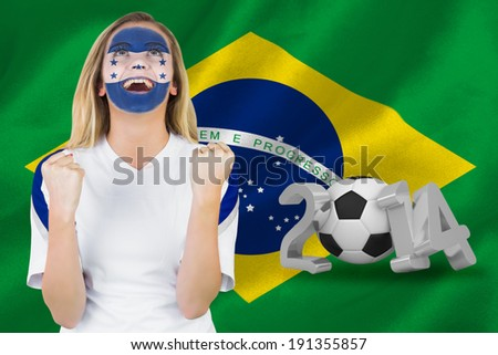 Excited honduras fan in face paint cheering against 2014 with brasil flag - stock photo