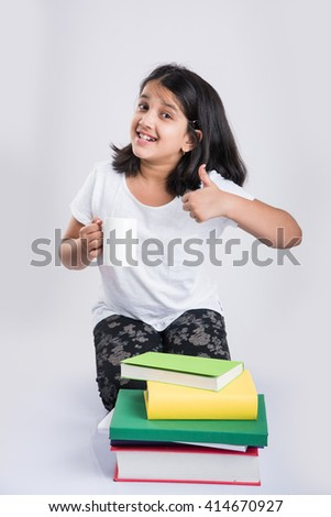 excited indian girl with a mug full of milk ready to start studies, cheerful indian small girl getting ready for studies or home work, isolated over white background - stock photo