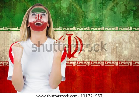 Excited iran fan in face paint cheering against iran flag in grunge effect - stock photo
