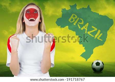 Excited japan fan in face paint cheering against football pitch with brazil outline and text - stock photo