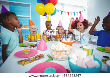 Excited kids enjoying a birthday party with lots of sweets - stock photo